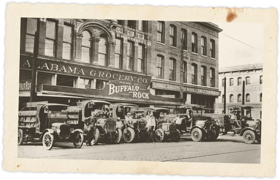 Buffalo Rock's truck fleet in front of Alabama Grocery, with president Jimmy C. Lee and employees