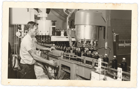 Future Buffalo Rock vice president Jimmy Wolfe operating a capping machine at the plant